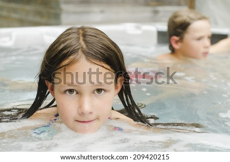Cute young girl relaxing in a hot tub - stock photo