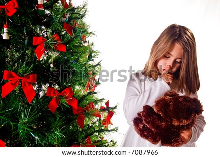 Cute young girl shushes her bear to keep a secret next to the Christmas tree
