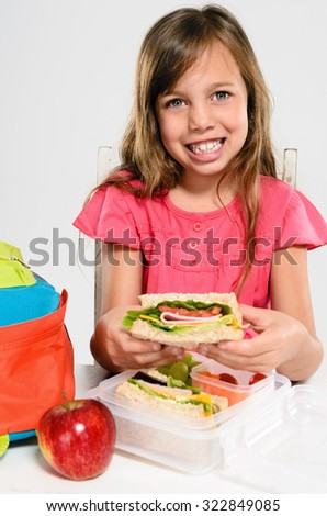 Cute young girl smiles and holds her healthy wholemeal sandwich over her lunch box and school backpack - stock photo