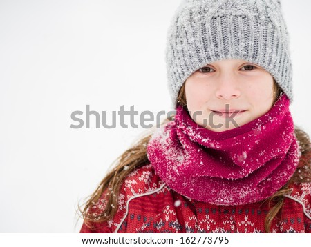 Cute young girl smiling in a snow storm