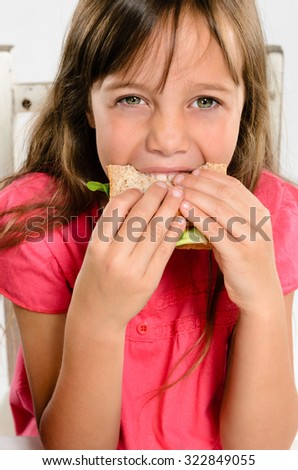 Cute young girl smiling while biting eating her wholemeal sandwich - stock photo