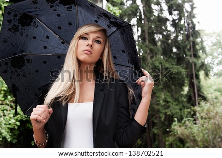 Cute Young girl standing in the rain holding umbrella - stock photo