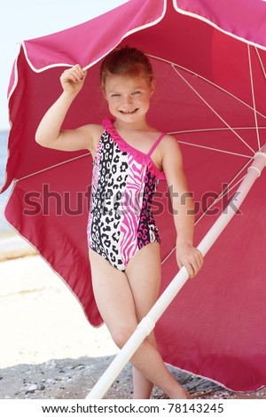Cute young girl standing in the shade of pink beach umbrella on sunny day.