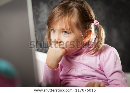 Cute young girl staring at laptop computer screen.