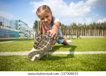 Cute young girl stretching on grass before running - stock photo