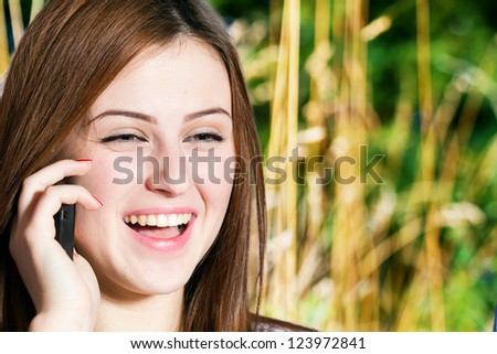 Cute young girl talking to phone - stock photo