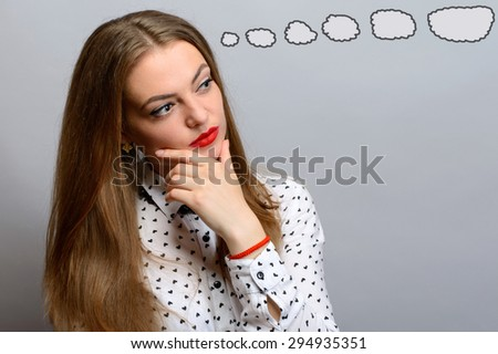 Cute young girl thinking an idea over grey background