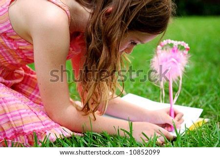 Cute young girl using fancy pen to write in journal outside - stock photo