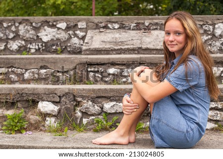 Cute young girl wearing a hat sitting on stone steps in a park. - stock photo
