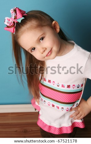 Cute young girl wearing a t shirt and matching hair bow, posing in studio with hands on hips - stock photo