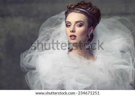 cute young girl wearing like sophisticated dame with creative romantic dress, elegant hair-style, shiny tiara, precious earrings and stylish make-up. Looking in camera with arrogant expression  - stock photo