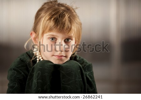 Cute young girl with big eyes in dress-up clothes chin on knees