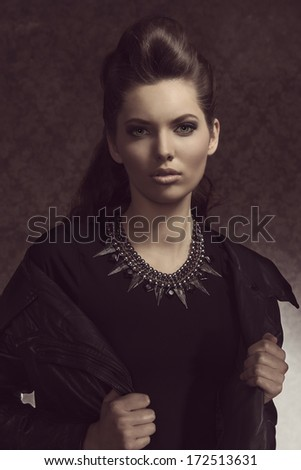 cute young girl with fashion casual modern rock style and long brown hair wearing leather jacket and big necklace looking in camera  - stock photo