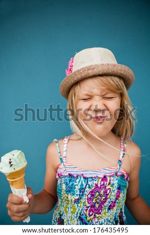 Cute young girl with funny expression holding ice cream cone outside against blue wall background - stock photo