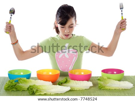 Cute young girl with lettuce and colourful bowls - stock photo