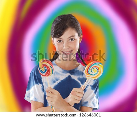 Cute young girl with two lollipops with a colorful background - stock photo