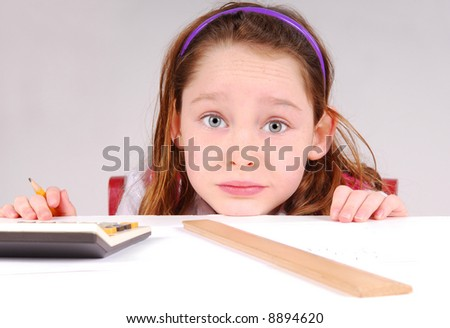 Cute young girl working on math homework at desk - stock photo