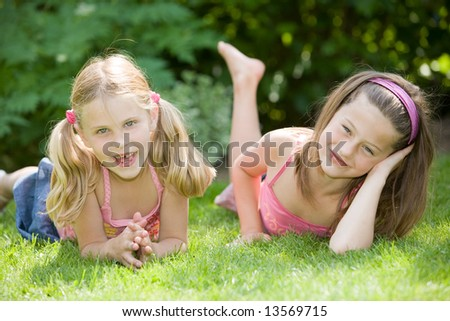 Cute young girls on a summer's day lying in the grass - stock photo