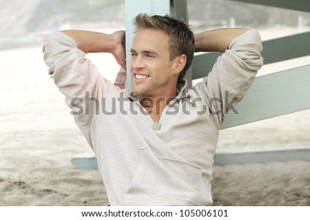 Cute young guy with nice smile relaxing outdoors - stock photo