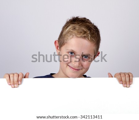 Cute young happy boy holding a blank board against white background and smiling - stock photo