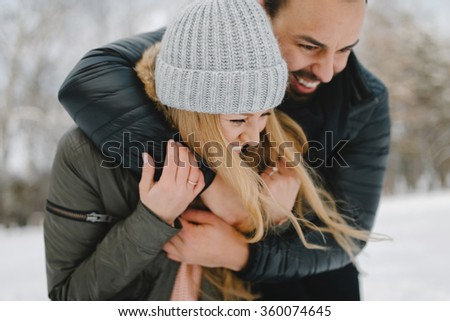Cute young hipster couple having fun in winter park on a bright day hugging each other and smiling - stock photo