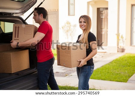 Cute young Hispanic couple loading their stuff in their car and moving to their new home - stock photo