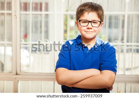 Cute young kid wearing glasses and casual clothes relaxing with his arms crossed at home - stock photo