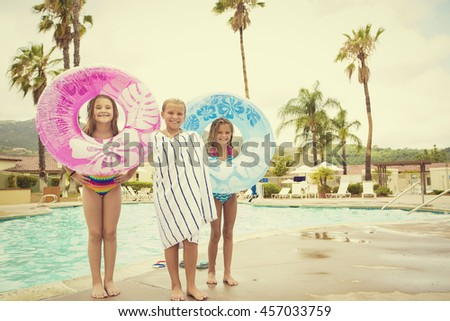 Cute young kids playing in the pool on a summer day. Warm tinted image - stock photo