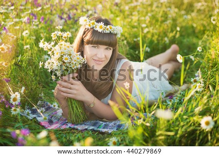 Cute young lady on a chamomile field with flower bouquet and wreath on the head.