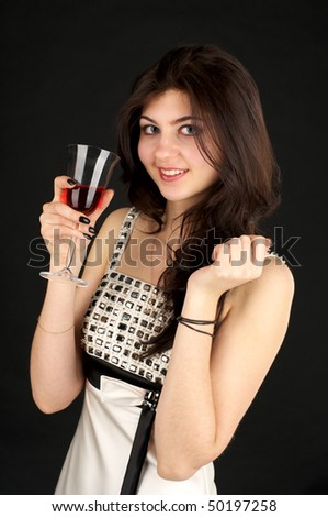 Cute young lady with glass of red wine over black background - stock photo
