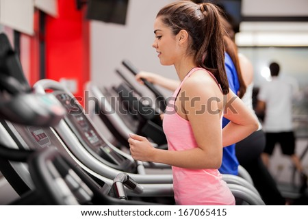 Cute young Latin woman exercising on a treadmill at a gym - stock photo