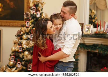 Cute young laughing family at home near the christmas tree in decorated room - stock photo