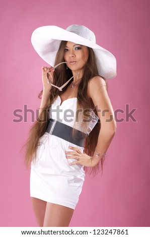 Cute young long-haired woman in the white dress and a big hat posing in studio - stock photo
