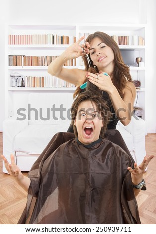 cute young male chubby child kid or boy shocked and surprised with face expression with long hair at smiling female hairdresser cutting his hair while he sitting in chair with bosco, fanny photo - stock photo