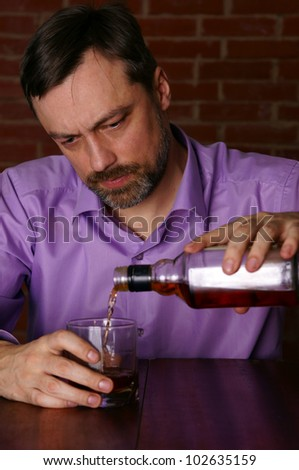 cute young man drinks whiskey at table - stock photo