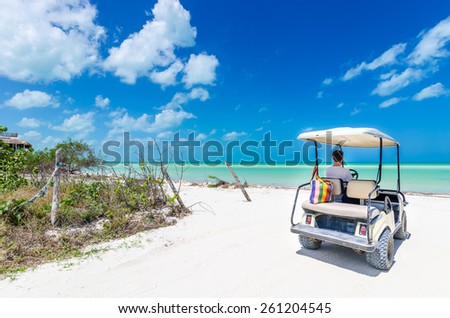 Cute young man driving golf cart back view at tropical white sandy beach during his Caribbean vacation on Holbox island, Mexico - stock photo