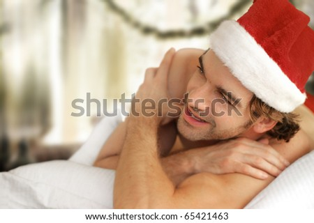 Cute young man in Santa cap laughing and smiling - stock photo