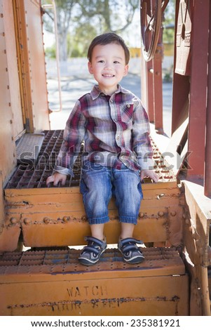 Cute Young Mixed Race Boy Having Fun Outside Sitting on Railroad Car Steps. - stock photo