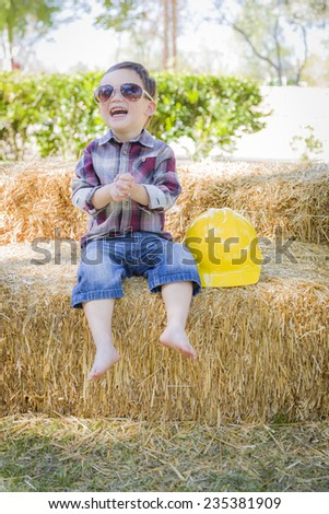 Cute Young Mixed Race Boy Laughing with Sunglasses and Hard Hat Outside Sitting on Hay Bale. - stock photo