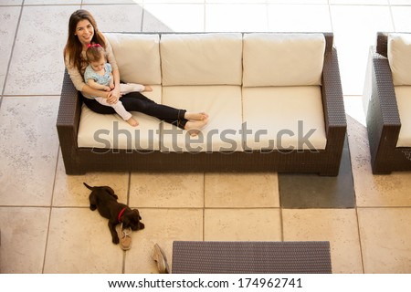 Cute young mother relaxing with her baby girl and her dog on a patio - stock photo