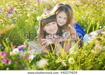 Cute young mother with daughter on a chamomile field with flower bouquet and wreath on the head.