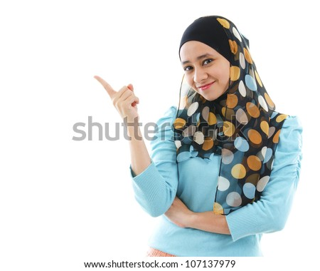 Cute young Muslim woman pointing on empty space, isolated on white - stock photo