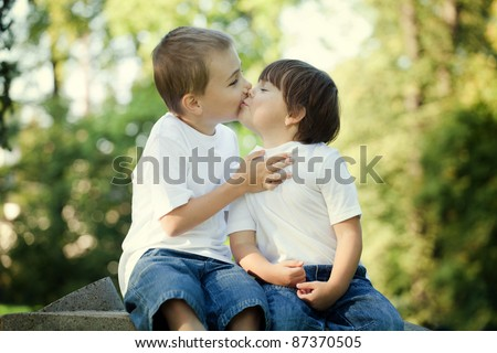 Cute young preschool boy and girl kissing outdoors with leafy, sunlit background.