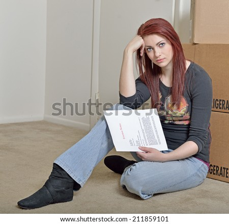 Cute young red-haired woman sitting on floor of home holding a generic eviction letter in front of cardboard boxes - stock photo