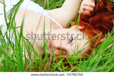Cute young redhead female lying on grass field at the park - stock photo
