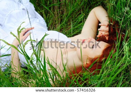 Cute young redhead female sleeping on grass field at the park - stock photo