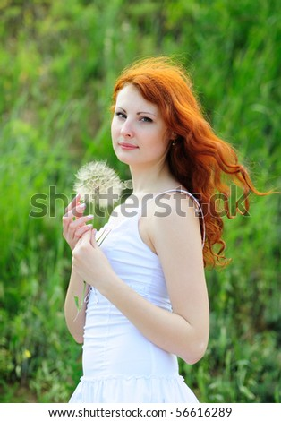 Cute young redhead female with big dandelion in her hands