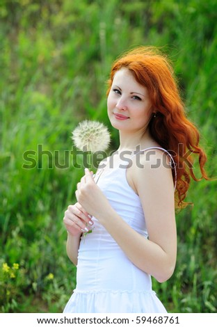 Cute young redhead female with big dandelion in her hands - stock photo