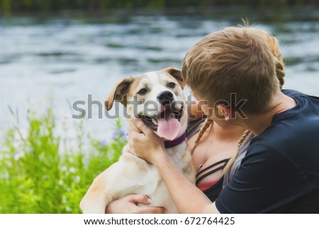 Cute young retriever in hands of his owners. Young Caucasian couple holding their dog in hands and patting it by river