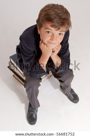 Cute young schoolboy sitting on top of a pile of books - stock photo